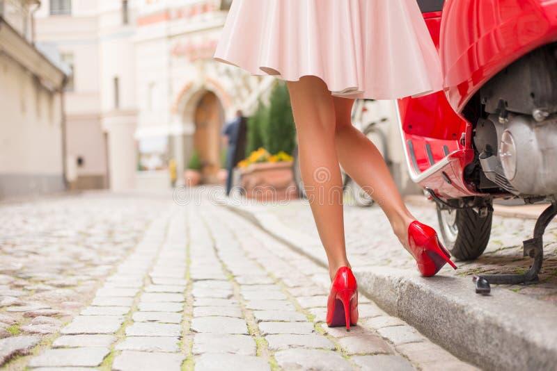 Mujer elegante y elegante al lado de la vespa roja brillante del moto fotografía de archivo libre de regalías