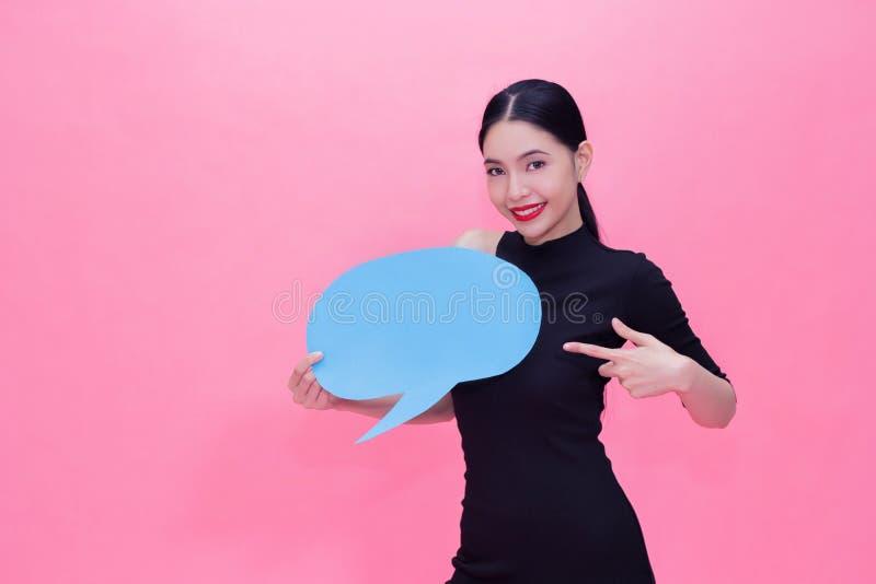 Mujer elegante y elegante hermosa y bastante asiática joven en el vestido negro de la moda que lleva a cabo discurso azul vacío d foto de archivo