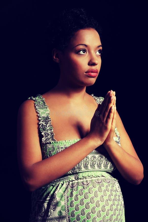 Mujer embarazada afroamericana joven que ruega imágenes de archivo libres de regalías
