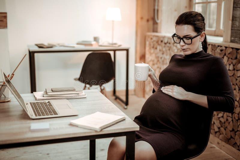Mujer embarazada agradable elegante que frota ligeramente su vientre imágenes de archivo libres de regalías