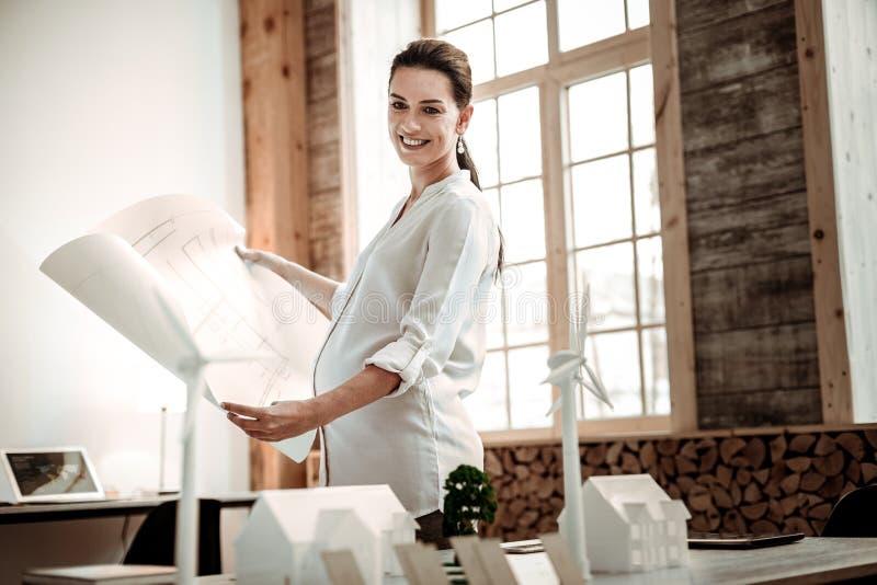 Mujer embarazada alegre que sostiene un modelo profesional imagen de archivo libre de regalías