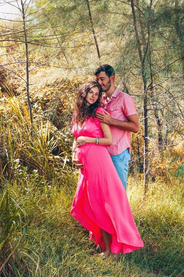 Mujer embarazada alegre y marido felices que se divierten al aire libre fotografía de archivo libre de regalías