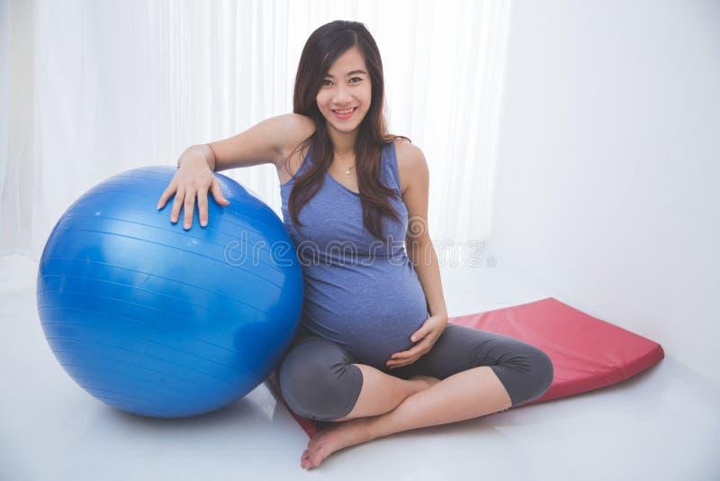 Mujer embarazada asiática hermosa que se sienta en una estera de la yoga, sosteniendo a imagenes de archivo