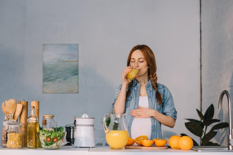 mujer embarazada atractiva que bebe el zumo de naranja fotografía de archivo libre de regalías