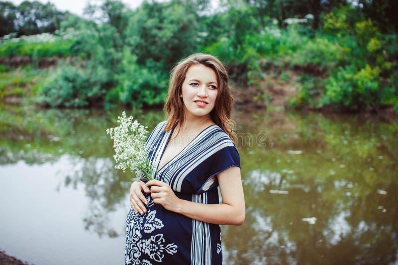 Mujer embarazada cerca del agua imagen de archivo