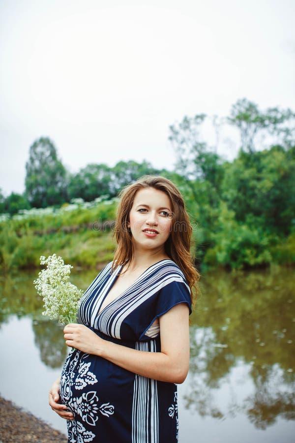Mujer embarazada cerca del agua fotos de archivo