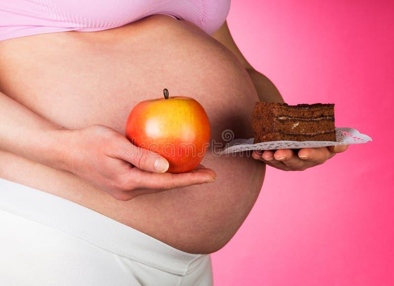 Mujer embarazada con Apple y la torta en el aislamiento fotos de archivo