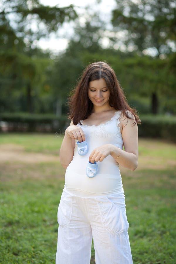 Mujer embarazada con botines imagen de archivo