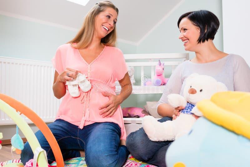 Mujer embarazada con el amigo en sitio anticipado del bebé fotos de archivo libres de regalías