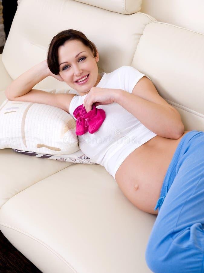 Mujer embarazada con el bootee del bebé fotos de archivo