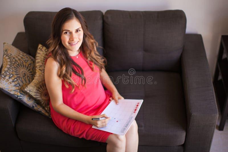 Mujer embarazada con el calendario imagen de archivo