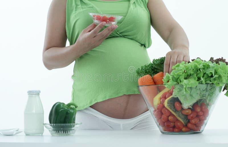 Mujer embarazada con el cuenco de ensalada. fotografía de archivo