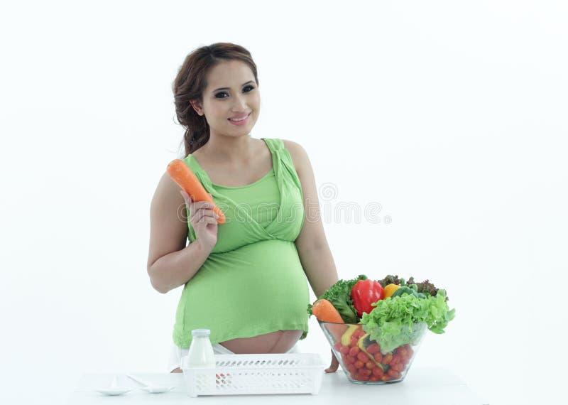 Mujer embarazada con el cuenco de ensalada. imagen de archivo libre de regalías