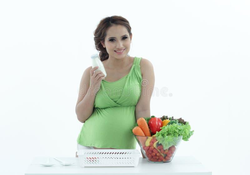 Mujer embarazada con el cuenco de ensalada. foto de archivo