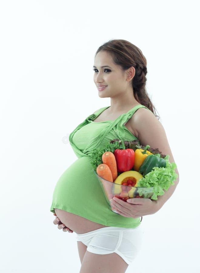 Mujer embarazada con el cuenco de ensalada. fotos de archivo libres de regalías