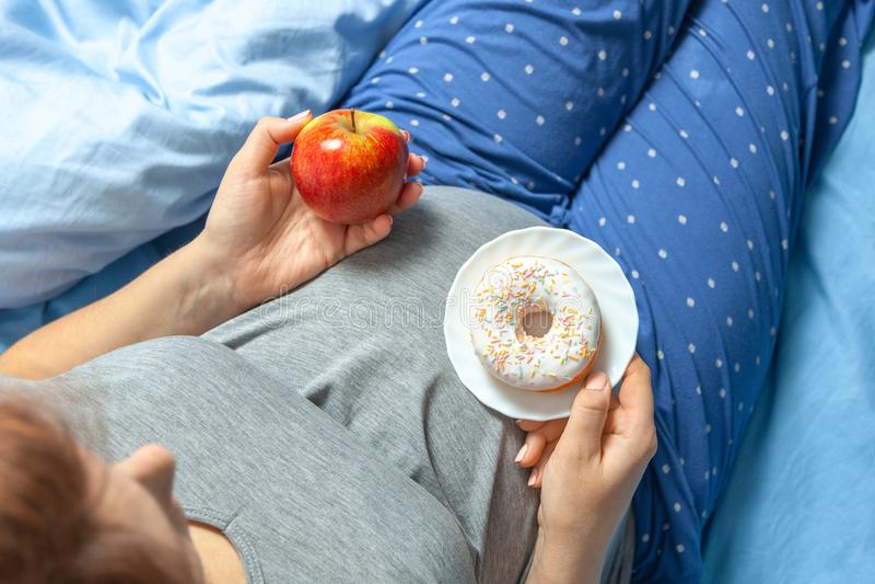 Mujer embarazada con el est?mago y sostener una manzana y un bu?uelo Dieta para las mujeres embarazadas fotos de archivo