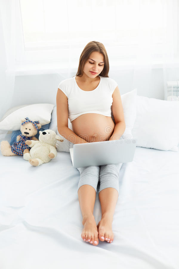 Mujer embarazada con el ordenador portátil Mujer embarazada hermosa Wo imagen de archivo