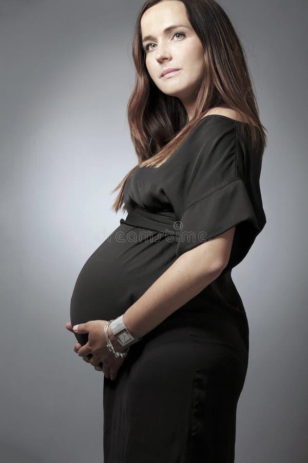 Mujer embarazada con el pelo oscuro largo en alineada negra. imagenes de archivo