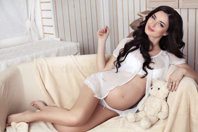Mujer embarazada con el pelo oscuro largo que presenta en interior acogedor imágenes de archivo libres de regalías