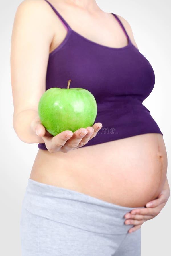 Mujer embarazada con la manzana verde a disposición imagenes de archivo