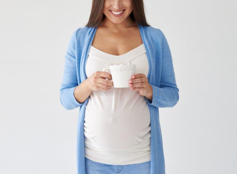 Mujer embarazada con la taza de té que presenta contra el fondo blanco i foto de archivo
