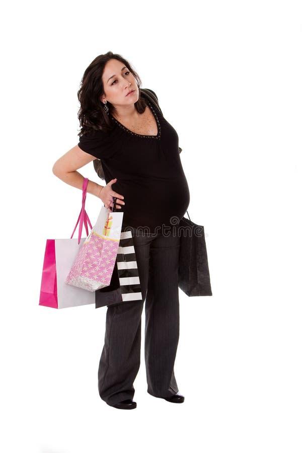 Mujer embarazada con los bolsos de compras fotografía de archivo