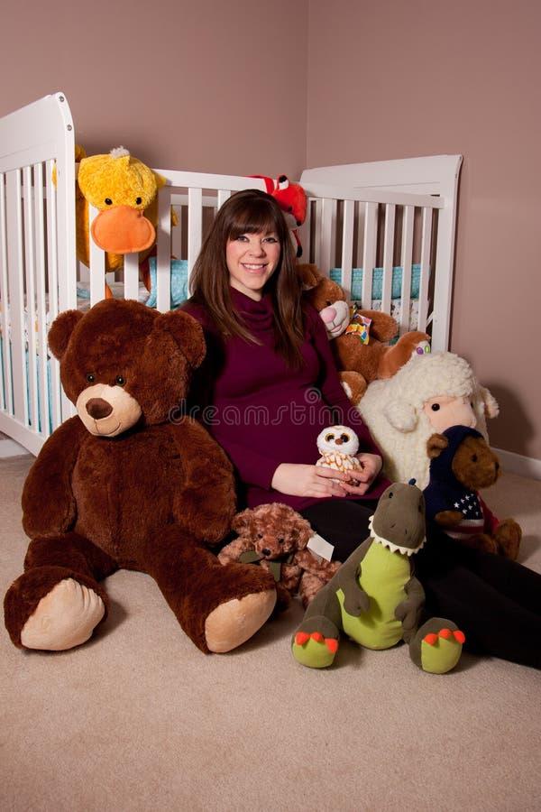 Mujer embarazada con los juguetes rellenos fotos de archivo