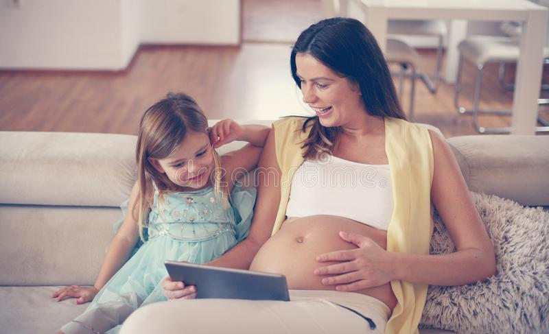 Mujer embarazada con su hija imagenes de archivo