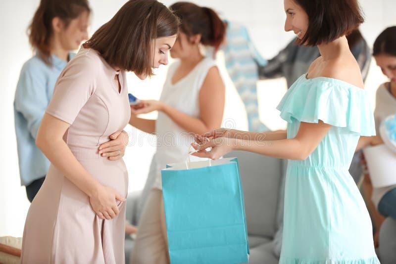 Mujer embarazada con sus amigos en el partido de fiesta de bienvenida al bebé fotos de archivo libres de regalías