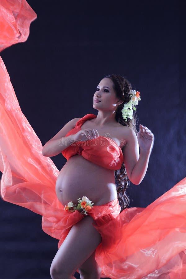 Mujer embarazada con un vestido rojo. fotografía de archivo