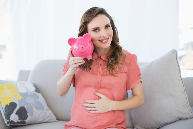 Mujer embarazada contenta que sacude la hucha rosada que se sienta en el sofá imagen de archivo libre de regalías