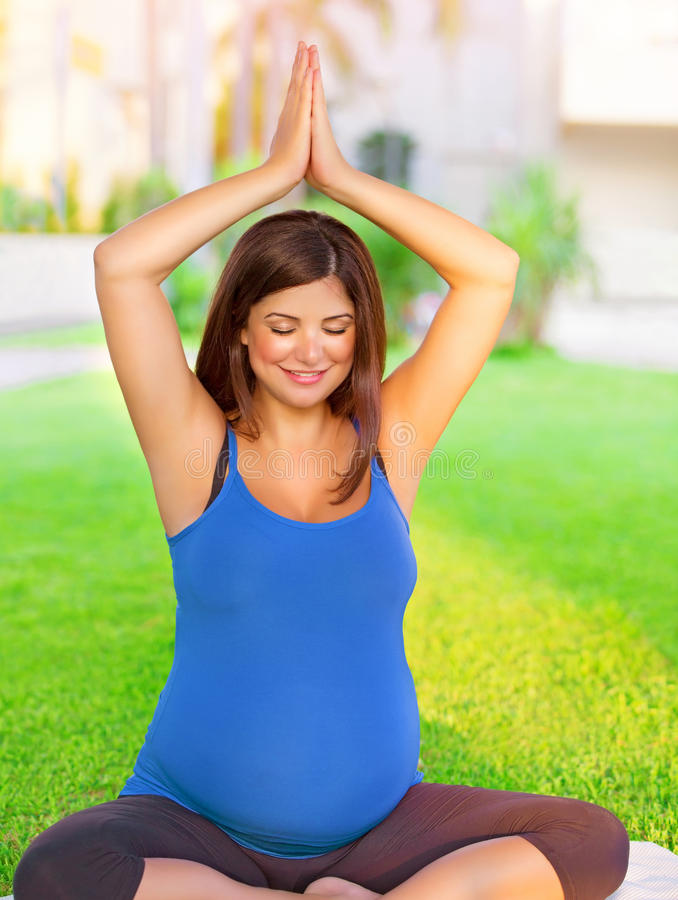 Mujer embarazada contratada a yoga al aire libre imagenes de archivo