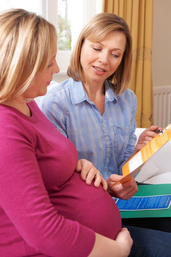 Mujer embarazada de Discussing Literature With de la partera en la visita casera fotografía de archivo libre de regalías