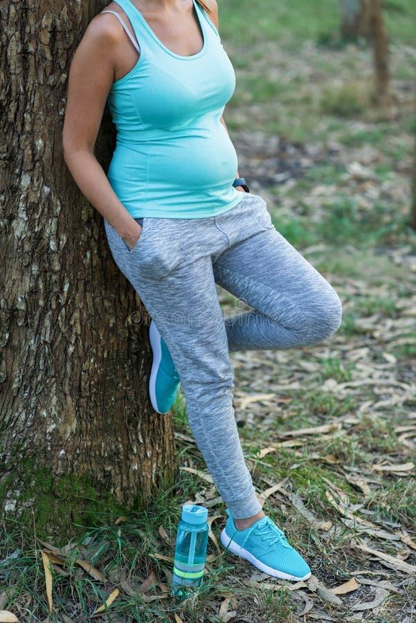 Mujer embarazada de la aptitud que descansa después de ejercitar imagenes de archivo