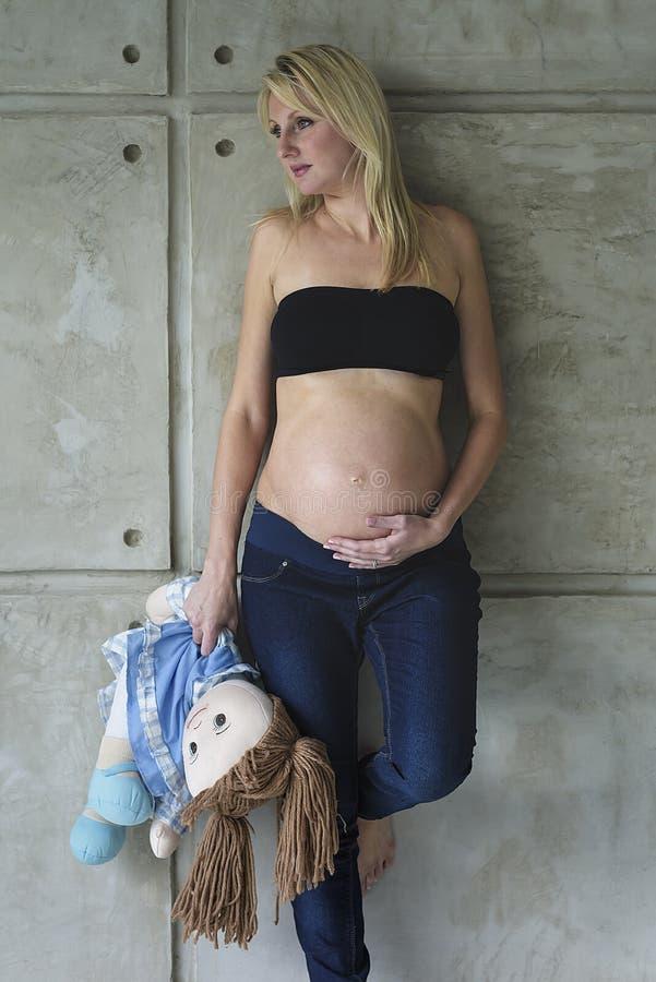 Mujer embarazada de los jóvenes con su niño nonato imágenes de archivo libres de regalías