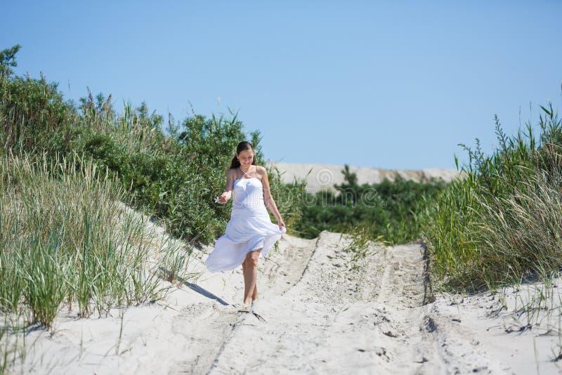 Mujer embarazada de los jóvenes en la playa imagen de archivo