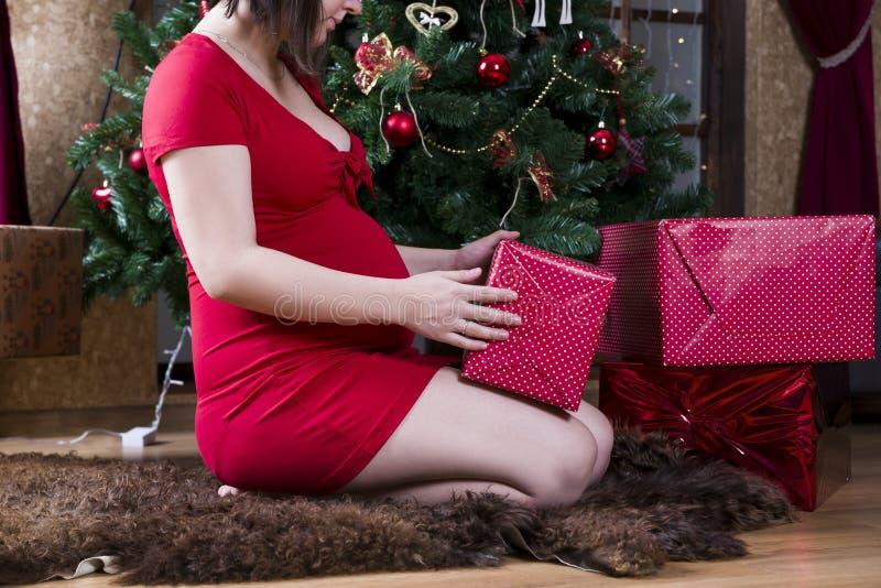 Mujer embarazada de los jóvenes en vestido rojo con las cajas de regalo que presentan en el fondo del árbol de navidad imagen de archivo