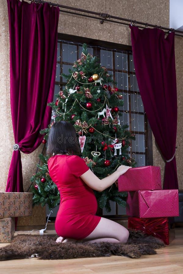 Mujer embarazada de los jóvenes en vestido rojo con las cajas de regalo que presentan en el fondo del árbol de navidad imágenes de archivo libres de regalías