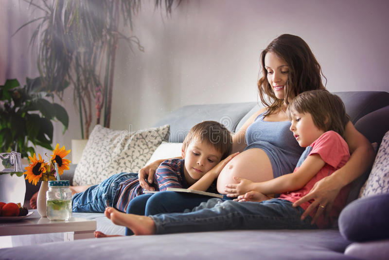 Mujer embarazada de los jóvenes, leyendo un libro en casa a sus dos muchachos fotografía de archivo