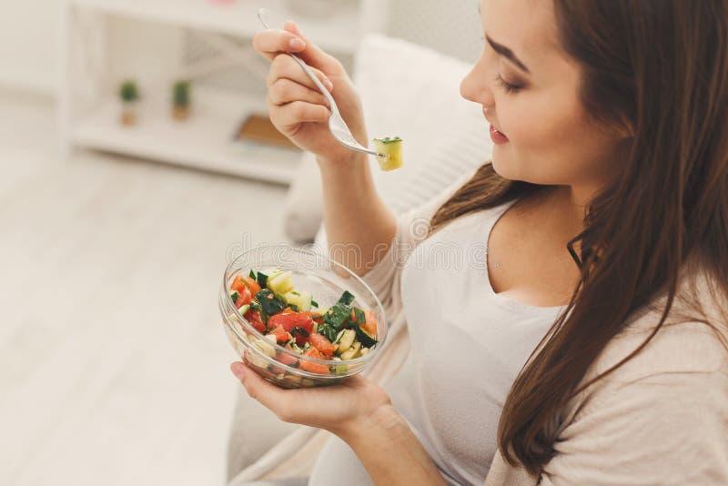 Mujer embarazada de los jóvenes que come la ensalada verde fresca imagenes de archivo