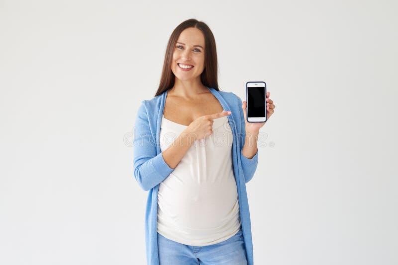 Mujer embarazada de los jóvenes que señala en el smartphone con la pantalla negra imagen de archivo