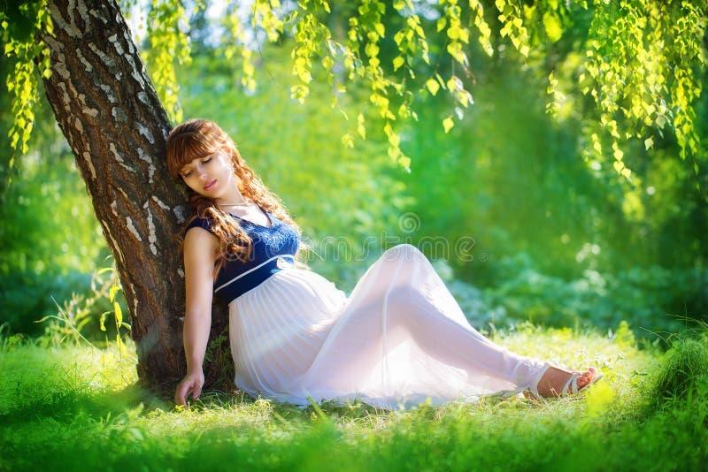 Mujer embarazada de los jóvenes que se relaja en parque al aire libre, pregnanc sano imágenes de archivo libres de regalías