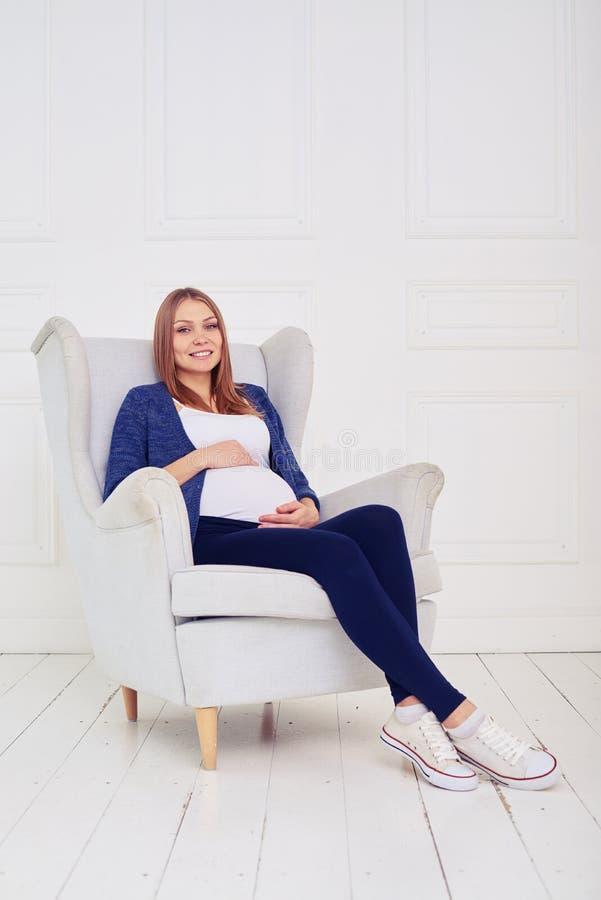 Mujer embarazada de los jóvenes que se sienta en la silla que lleva cómodo casual imagenes de archivo
