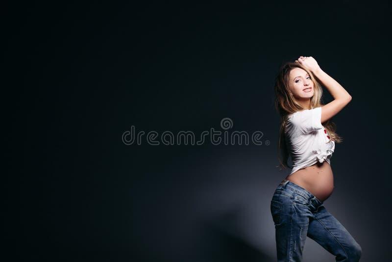 Mujer embarazada de moda con la panza desnuda fotografía de archivo libre de regalías