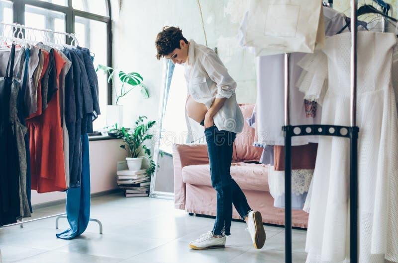 Mujer embarazada de moda que intenta en una sala de exposición fotos de archivo