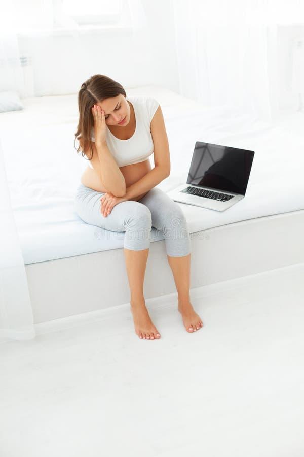 Mujer embarazada deprimida con un ordenador portátil mientras que se sienta encendido foto de archivo