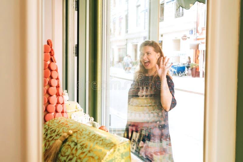 Mujer embarazada divertida en la ventana de una tienda de pasteles con los macarrones foto de archivo