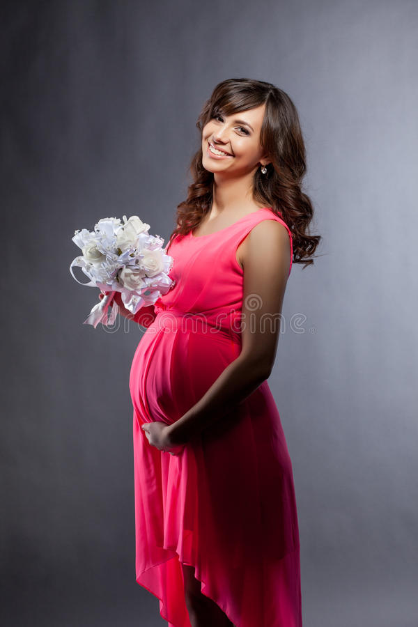 Mujer embarazada elegante vestida que sonríe en la cámara fotografía de archivo libre de regalías