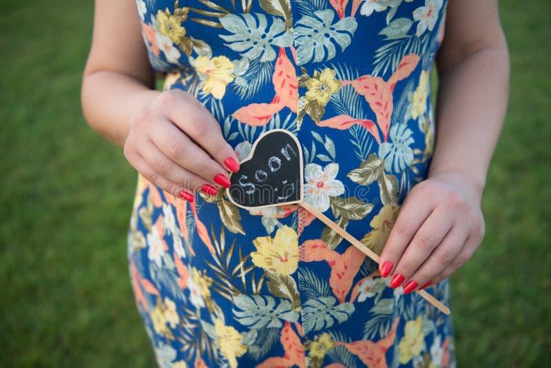Mujer embarazada, embarazo, padre y madre, nuevo bebé que espera, bebé recién nacido, zapatos del bebé recién nacido fotografía de archivo