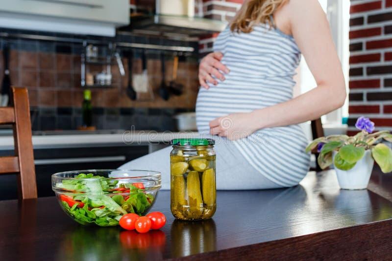 Mujer embarazada en cocina y pepinos conservados en vinagre Alimento sano fotos de archivo libres de regalías
